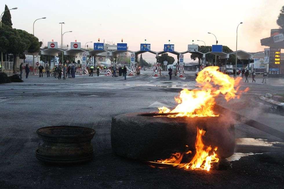 Barricada de neumáticos quemados en uno de los accesos a MercaBarna, Barcelona.